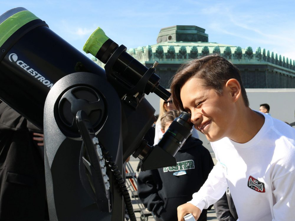 A boy looks through a telescope at the Griffith Observatory.