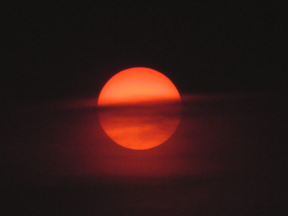 Sun behind clouds. Photo by Mourya (https://unsplash.com/photos/EwawqhV2Doc)